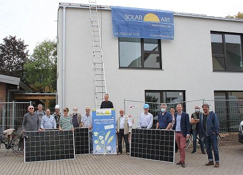 Eine Gruppe Menschen steht vor dem neuen Kindergartengebäude und präsentiert Solarmodule